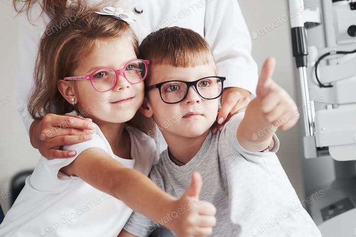 Ärztin umarmt ihre kleinen Patienten. Gläser sind perfekt ausgewählt