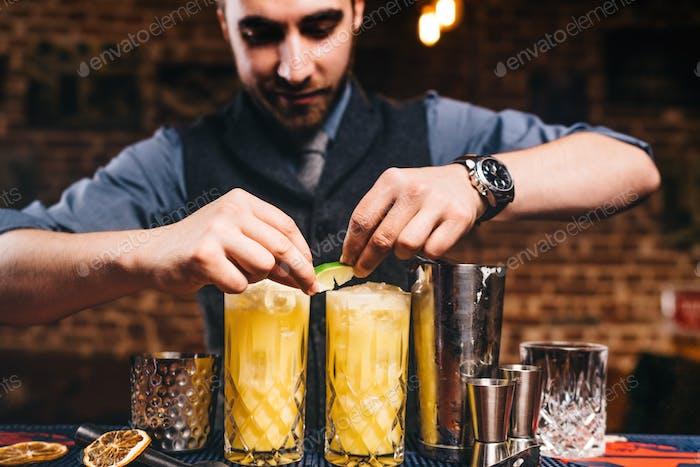 Professionelle Barkeeper garnieren mit Limettencocktails