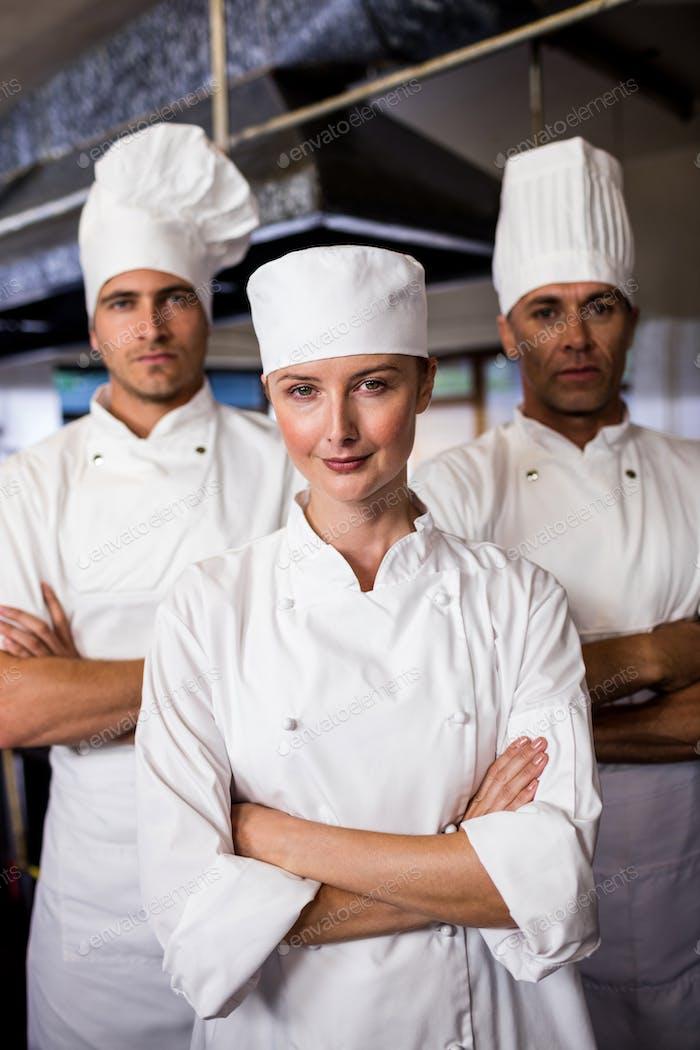 Grupo de chefs de pie con los brazos cruzados en la Cocina del hotel