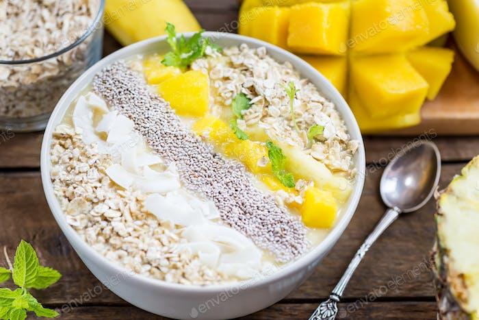 Mango, Banane, Ananas und Haferflocken Smoothie in der Schüssel
