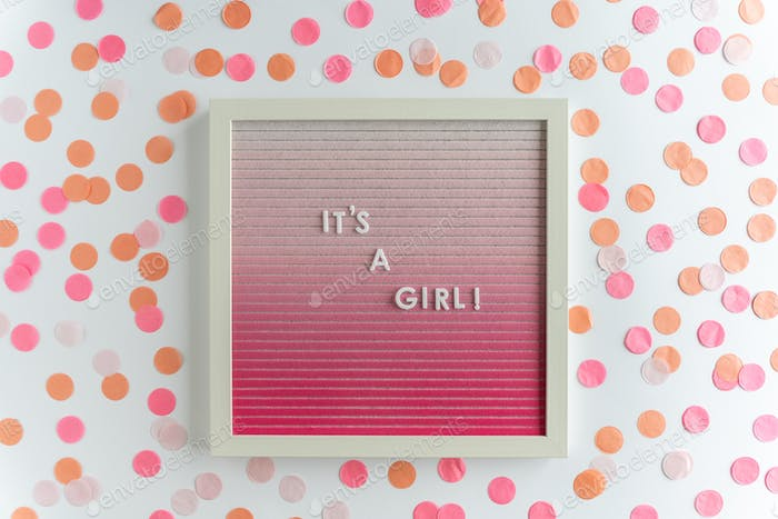 pink letter board with the words It's a girl, with confetti