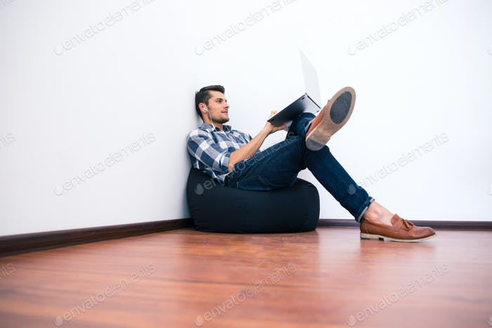 Young man in casual cloth using laptop on bag chair
