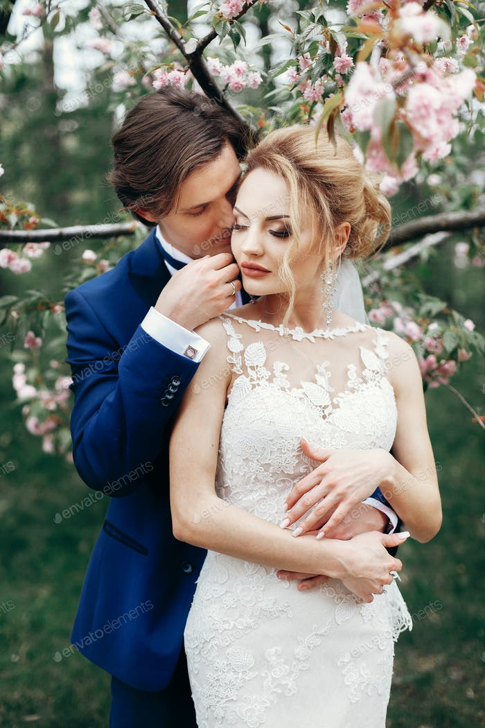 Handsome groom touching and embracing beautiful blonde bride