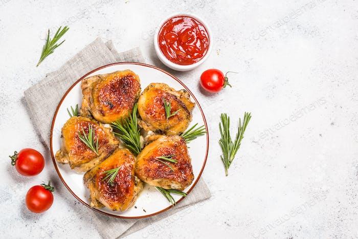 Muslos de pollo al horno con hierbas en plato blanco
