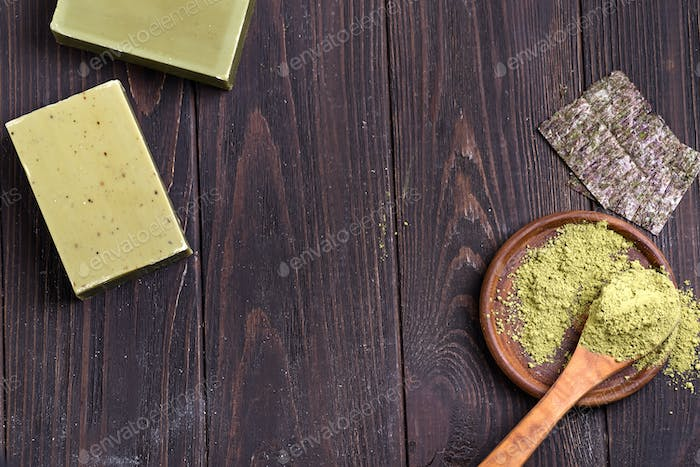 Bars of green natural olive oil soaps with green powder and dry seaweed on dark wooden background