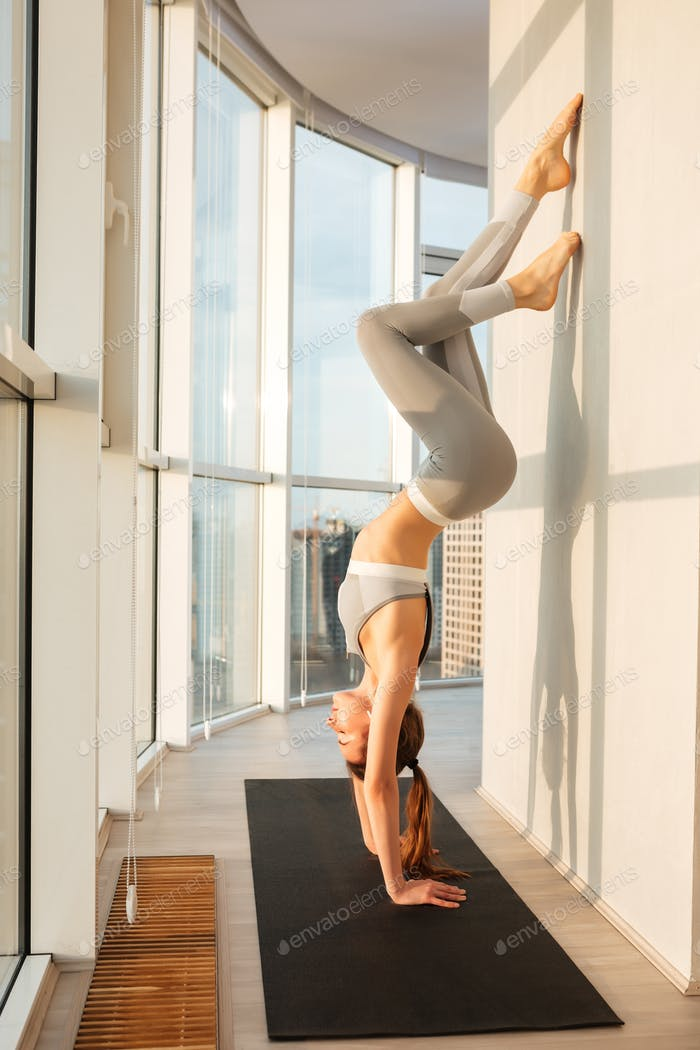 Lady in sporty top and leggings standing on hands practicing yoga on yoga mat at home with city view