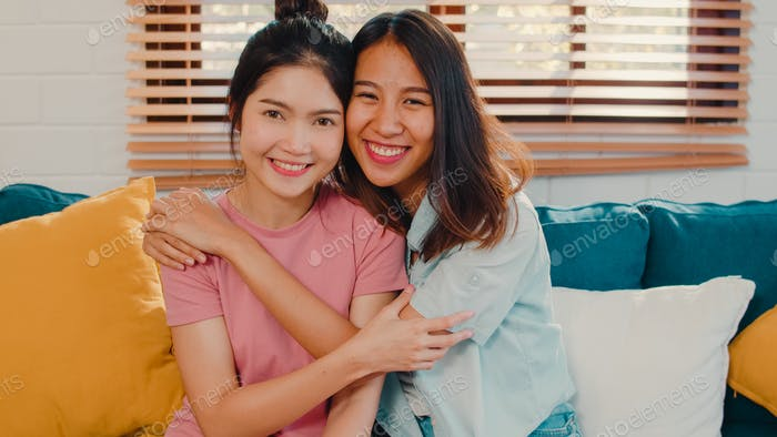 Amante asiático femenino relajarse sonrisa con dientes mirando a la cámara.