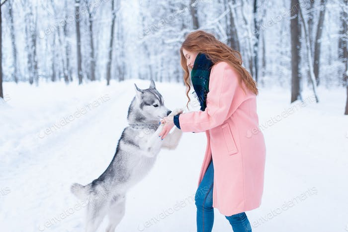 Pretty woman with playful husky dog