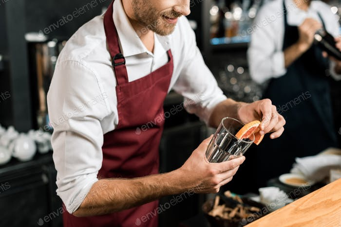 cropped view of smiling barman decorating glass with grapefruit slice