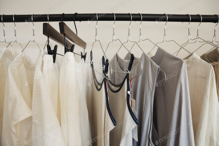 Close up of a selection of clothes in natural colours on a rail in a boutique.