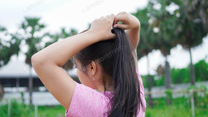 asiatische Läuferin bindet Haare im Stadion