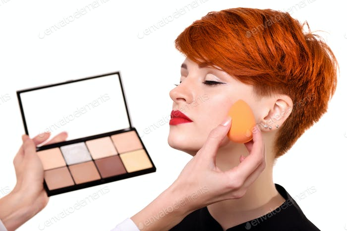 Makeup artist applying foundation on young woman's face using sp