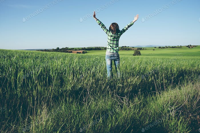 Young woman alone in a green field