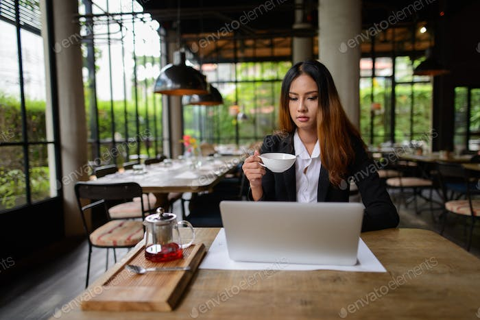 Young Asian businesswoman drinking coffee while working