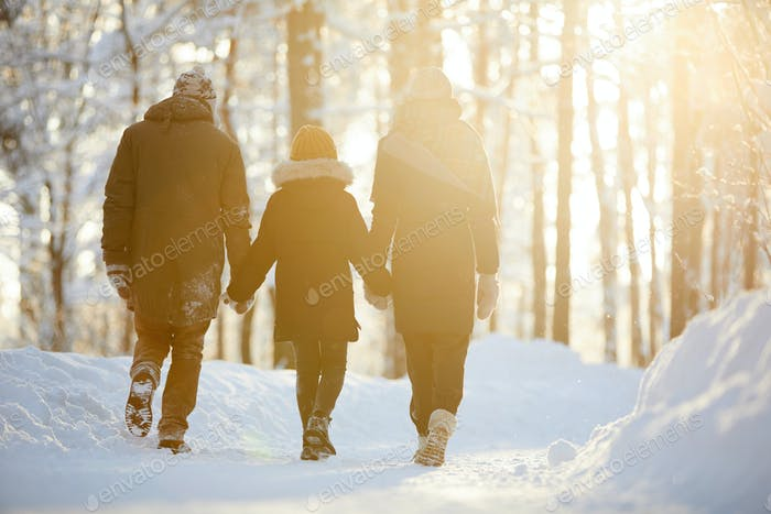 Family Enjoying Walk in Winter Forest