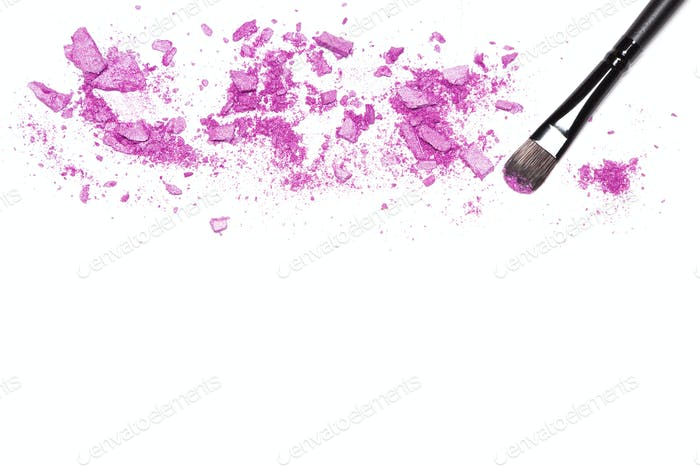 Makeup brush and purple eye shadow on white with space for text