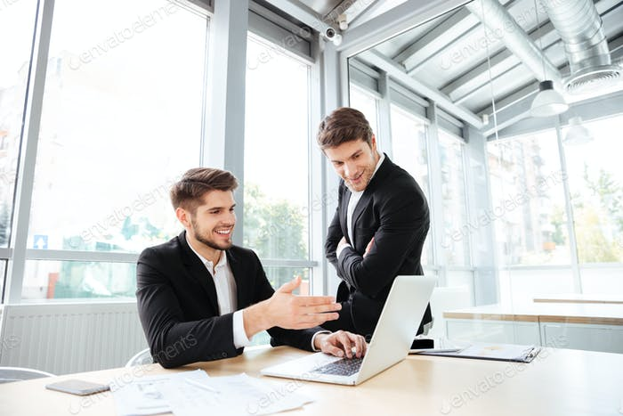 Two happy young businessmen talking and using laptop