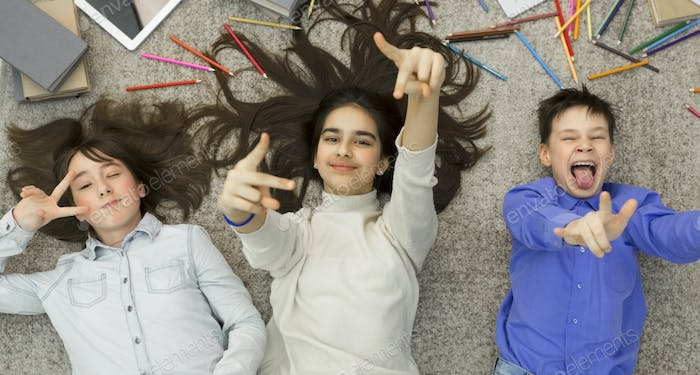 Joyful kids fooling, lying on carpet and having fun