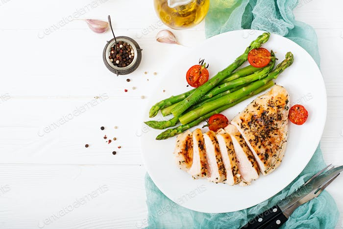 Chicken fillet cooked on a grill and garnish of asparagus