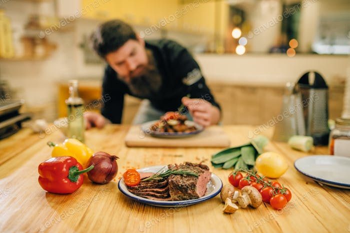 Chef decorates with herbs a meat dish for gourmets