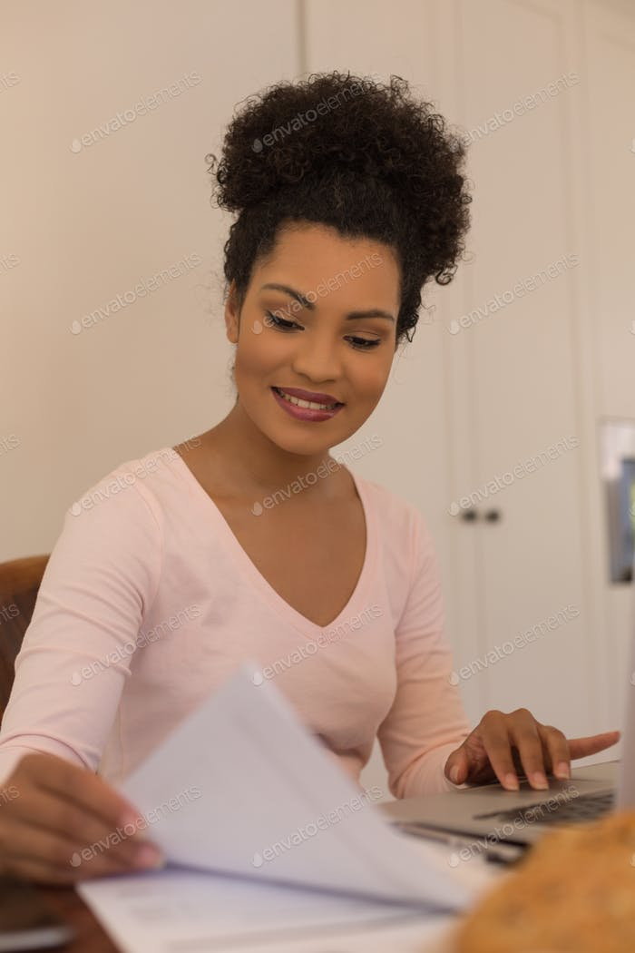 Front view of African American beautiful woman looking at form while using laptop at home