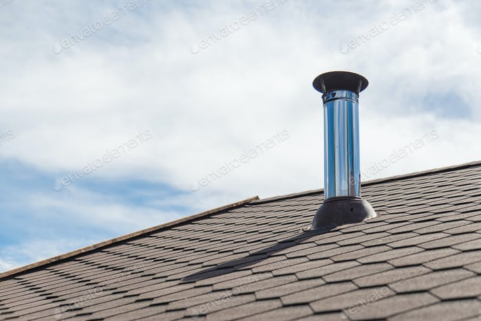 Chimney pipe from stainless steel on the roof of the house