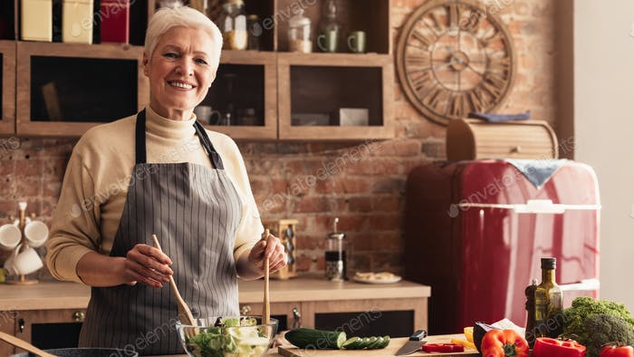 Portrait of smiling elderly woman cooking fresh vegetable salad in kitchen