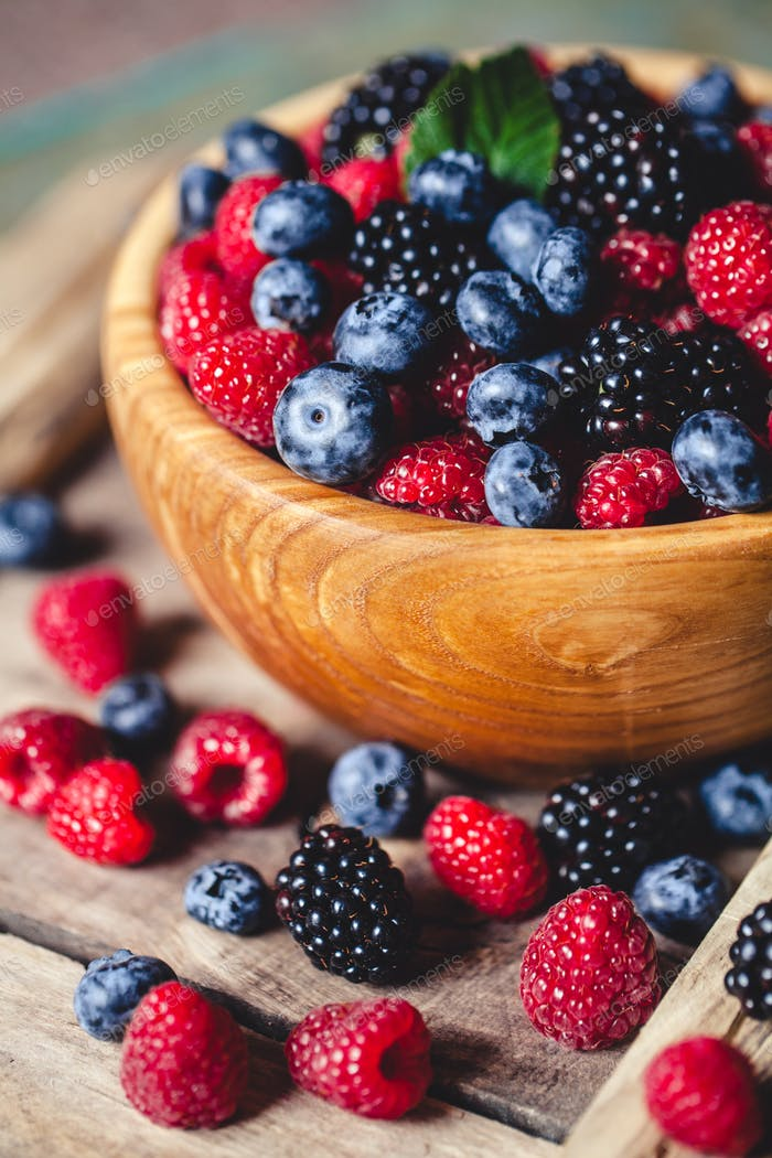 blueberries and raspberries, blackberry in a wooden bowl on old wood background