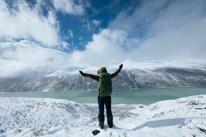 HikingCheering woman hiker hiking in snowing winter mountains