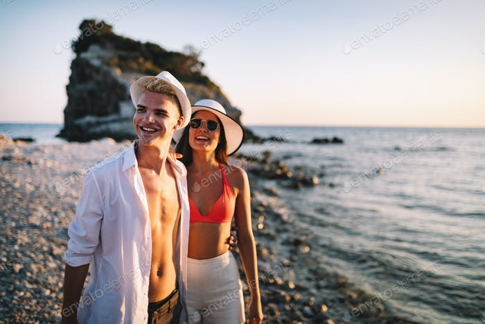 Happy young couple in love walking on seashore on vacation
