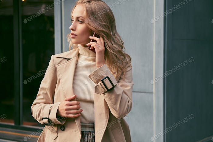 Attractive casual blond girl in trench coat talking on cellphone dreamily looking aside outdoor
