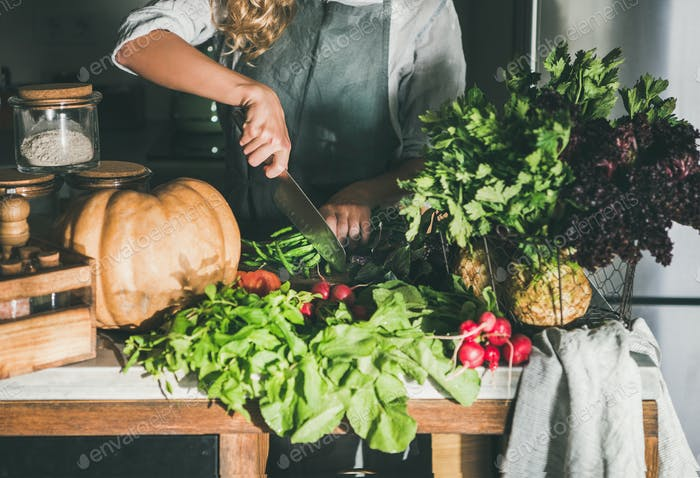 Female in apron cutting various vegetable ingredients on counter