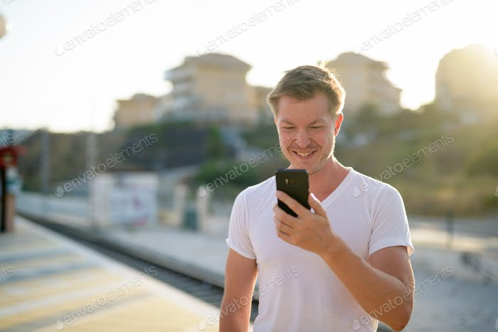 Happy man using mobile phone outdoors