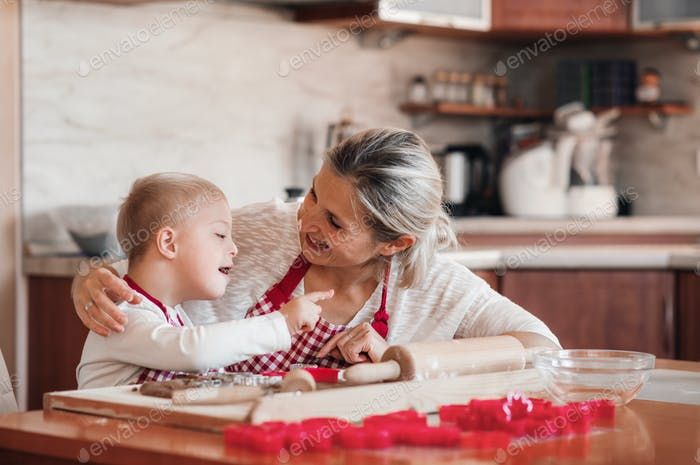 A happy handicapped down syndrome child with his mother indoors baking.