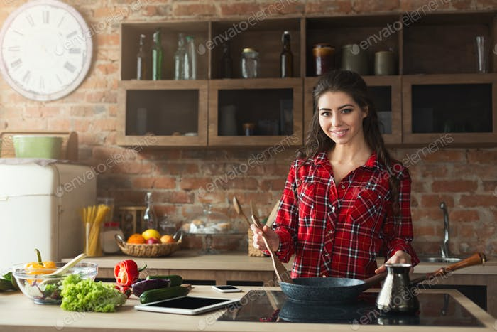 Happy woman preparing healthy food in the home kitchen