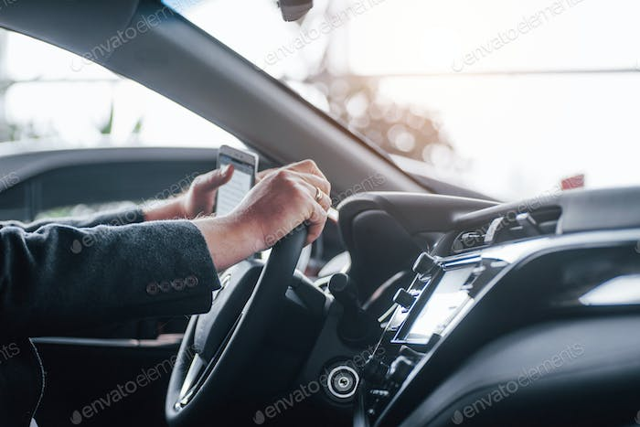 Cropped photo of businessman in the car with smartphone n hand