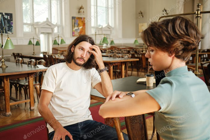 Young casual male student thoughtfully taking verbal exam to teacher in lecture room of university
