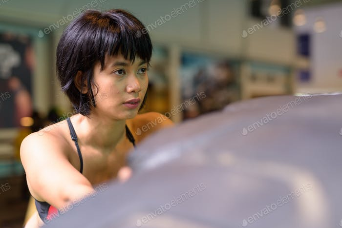 Asian fitness woman pushing and flipping wheel truck tire at gym