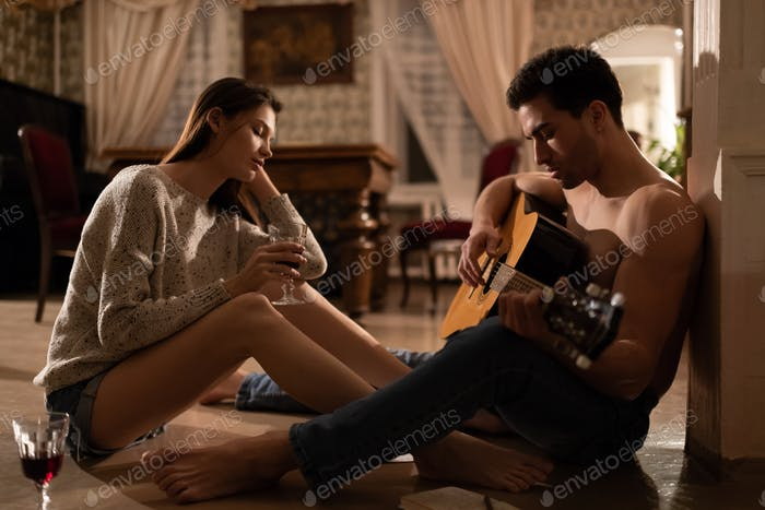 Relaxed woman listening to boyfriend playing guitar at home