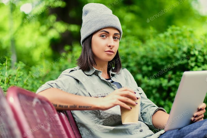Female holds tablet PC and coffee in a paper cup.