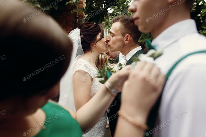 Beautiful bride in vintage wedding dress putting on boutonniere on handsome groom