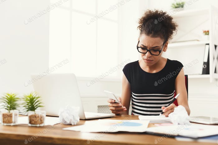 Serious woman making notes in office