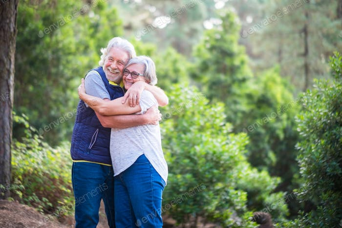 Handsome senior couple hugging in the woods enjoying outdoor excursion.