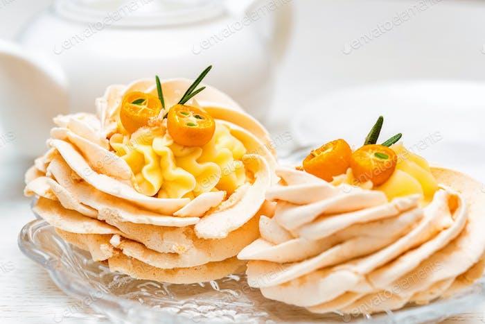 Meringue cake decorated with kumquat and tea