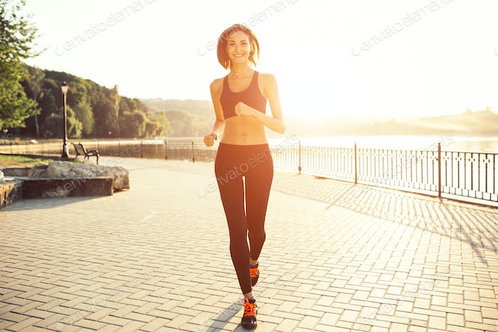 Woman running by the lake at sunset