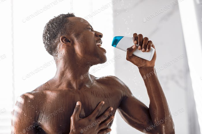 Black Man Singing In Shower Holding Shampoo Bottle Like Microphone