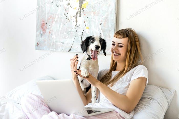 retrato de mujer feliz jugando con el cachorro en la mañana en casa