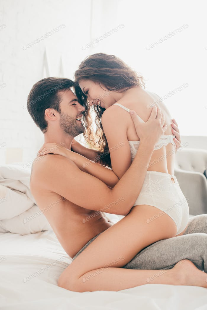 happy seductive young couple hugging on bed