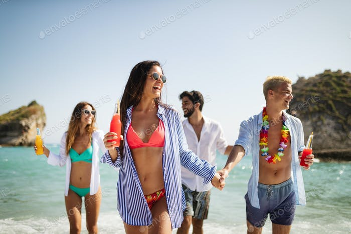 Group of happy friends on vacation having fun on beach in summer