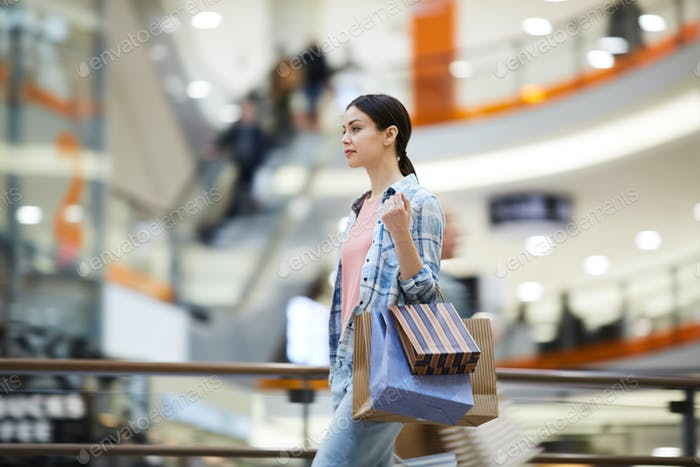 Young woman buying gifts in shopping mall